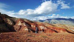 Молодая туристская женщина идет в красные каменные горы Нереальный сценарный ландшафт и облачное небо в видеоматериал
