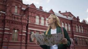 Молодая туристская женщина смотря карту около музея Москвы России положения исторического сток-видео