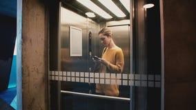 Молодая уверенно женщина входит в лифт, кнопку, дверь закрывает и она едет вниз с использования мобильного офиса app smartphone сток-видео