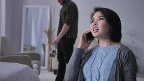 Молодая унылая азиатская девушка говорит агрессивно на телефоне используя smartphone, портрет, пьяный супруга в fps предпосылки 5 сток-видео