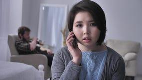 Молодая унылая азиатская девушка тревожено набирает номер, вызывает smartphone, портретом, взглядами на камере, пьяном супруге в акции видеоматериалы