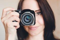Молодая усмехаясь девушка брюнет с камерой Стоковое фото RF