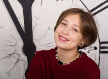 Молодая усмехаясь девушка на предпосылке часов стоковая фотография