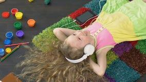 Молодая усмехаясь девушка поя любимую песню в больших белых наушниках, наслаждение акции видеоматериалы