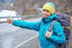 Молодая усмехаясь девушка путешествует в горах останавливает автомобиль на дороге путешествовать, поднимает его руку стоковые изображения