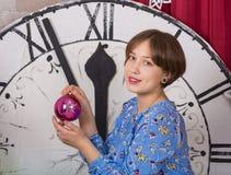 Молодая усмехаясь девушка с игрушками стеклянные шарики на предпосылке часов Нового Года стоковое фото