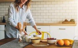 Молодая усмехаясь домохозяйка стоя в кухне около таблицы варит обедающий, очищая блюда Девушка делает завтрак Стоковые Фото