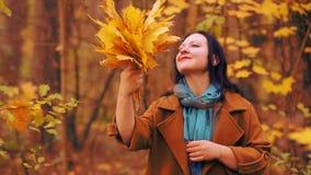 Молодая усмехаясь женщина брюнета в парке осени с кленовыми листами в руках видеоматериал
