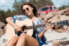 молодая усмехаясь женщина в игре солнечных очков акустической стоковые фото