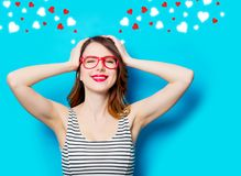 Молодая усмехаясь женщина в стеклах и абстрактных сердцах Стоковая Фотография