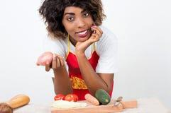 Молодая усмехаясь женщина держа свежие овощи в ее кухне стоковое фото