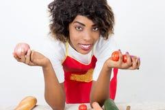 Молодая усмехаясь женщина держа свежие овощи в ее кухне стоковое изображение rf