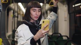 Молодая усмехаясь женщина имея видео- звонок во время ехать публично переход Предпосылка светов города сток-видео