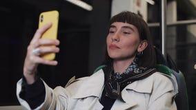 Молодая усмехаясь женщина имея видео- звонок во время ехать публично переход Она развевает ее рука и беседы к ее друзьям видеоматериал