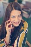Молодая усмехаясь женщина имея переговор на умном телефоне стоковое изображение rf