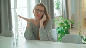 Молодая усмехаясь женщина используя телефон дома видеоматериал