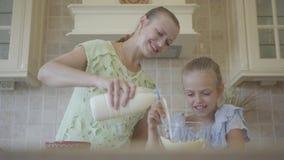 Молодая усмехаясь женщина и ее маленькая дочь варя торт дома в кухне Мать промежутка времени муки девушки смешивая видеоматериал