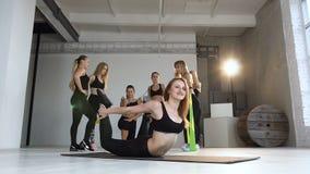 Молодая усмехаясь женщина нагревая сгабривать протягивающ их заднюю часть держа ноги и разрабатывая в занятиях йогой спортзала видеоматериал