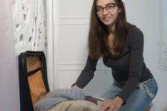 Молодая усмехаясь женщина пакует чемодан для отключения к холодной стране в Россию в зиме она смотрит стоковое фото rf