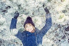 Молодая усмехаясь женщина под снежным хвойным деревом стоковая фотография
