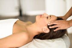 Молодая усмехаясь женщина получая головной массаж в спа-центре Стоковые Изображения RF