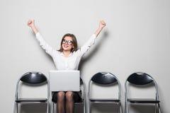 Молодая усмехаясь женщина работника офиса сидя на деревянном стуле пола используя передвижной портативный компьютер с поднятыми р Стоковые Фотографии RF