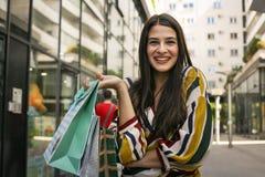 Молодая усмехаясь женщина стоя на улице с хозяйственными сумками Стоковые Фотографии RF