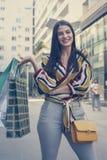 Молодая усмехаясь женщина стоя на улице с хозяйственными сумками Стоковое фото RF