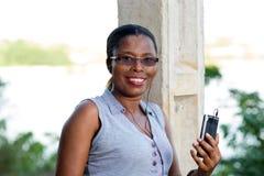 Молодая усмехаясь женщина с мобильным телефоном стоковая фотография