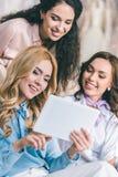 Молодая усмехаясь невеста и bridesmaids выбирая платья и смотря таблетку в свадьбе стоковое фото rf