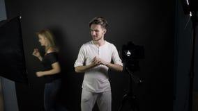 Молодая усмехаясь стрельба человека vlogger для его vlog в профессиональной студии пока подруга проходит через photobomb рамки - сток-видео