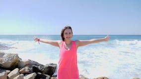 Молодая усмехаясь счастливая девушка распространяя ее оружия пока стоящ на скалистом пляже Волны ударяя утесы Брызгать воды акции видеоматериалы