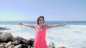 Молодая усмехаясь счастливая девушка распространяя ее оружия пока стоящ на скалистом пляже Волны ударяя утесы Брызгать воды ( сток-видео