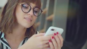 Молодая успешная женщина смотрит в телефон и улыбки видеоматериал