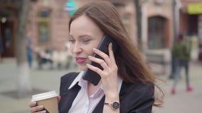 Молодая успешная коммерсантка в костюме используя умный телефон в городе городском, профессиональный женский работодатель разгова акции видеоматериалы