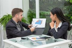 Молодая успешная пара дела говорящ и осматривающ документ Стоковая Фотография