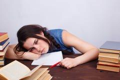 Молодая утомленная пробуренная женщина студента сидя на таблице с текстом Стоковые Изображения