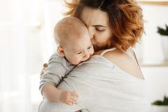 Молодая хорошая смотря мать обнимает и утихомиривает ее плача младенца Ребенок кричащий и плача на плече матери Сцена  Стоковая Фотография