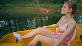 Молодая худенькая дама едет катамаран в реке парка летом на каникулах видеоматериал