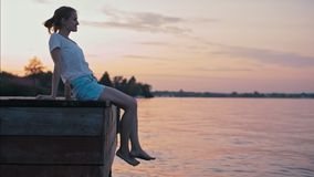 Молодая худенькая дама сидеть надводный на зареве захода солнца лета и ослаблять сток-видео