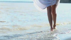 Молодая худенькая девушка с босыми ногами идя модельная походка на песчаном пляже моря Удержание рук, белое платье женщина ударов сток-видео