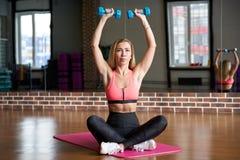 Молодая худенькая длинн-с волосами блондинка сидит на циновке спорт с гантелями в ее руках и strenuously выполняет тренировки стоковая фотография rf