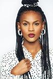 Молодая чернокожая женщина касаясь ее традиционному стилю причёсок пуков Стоковые Изображения RF
