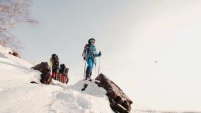 Молодая шестерня альпиниста полностью с поляками лыжи в руках стоит на снежной верхней части горы и насладилась взглядом сток-видео