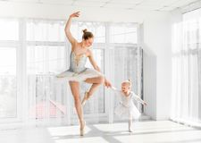 Молодая шикарная балерина с ее маленькими танцами дочери в студии Стоковая Фотография