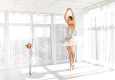 Молодая шикарная балерина с ее маленькими танцами дочери в студии Стоковые Изображения RF