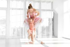 Молодая шикарная балерина с ее маленькими танцами дочери в студии Стоковые Изображения