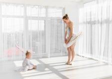 Молодая шикарная балерина с ее маленькими танцами дочери в студии Стоковое фото RF