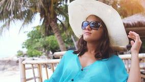 Молодая шляпа и солнечные очки элегантной женщины нося на празднике, сидя в кафе пляжа Стоковое Фото