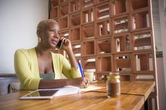 Молодая элегантная и красивая черная Афро-американская бизнес-леди работая онлайн говорить на мобильном телефоне на кофейне прини стоковая фотография